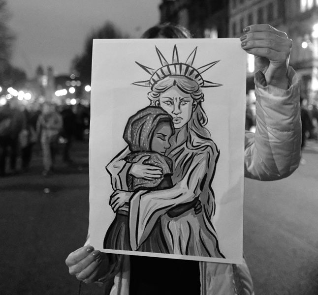 Cross Lady Liberty comforts refugee child. Seen in London at rally against Trump's travel ban, 30 Jan 2017.